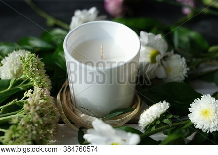 White Scented Candle And Delicate Flowers. Home Fragrances For Relaxation And Calm. Flower Fragrance