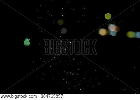 Defocused Round Bokeh Of City Street Lights, Headlights Of Passing Cars At Night. Multi-colored Boke