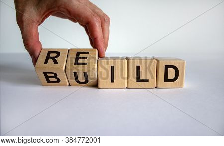 Concept Word 'rebuild' On Cubes On A Beautiful Wooden Table. Male Hand. White Background. Business C