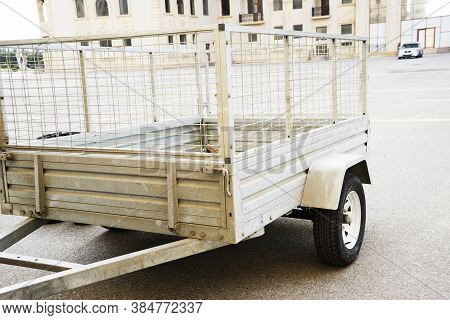 Car Trailer. Car Trailer With Two Wheel Axle, Loaded Silver Car Trailer At The Storage Place In A Co