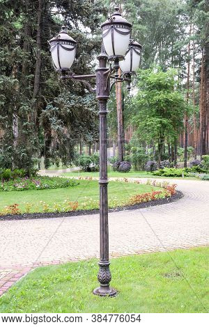Antique Vintage Iron Lamppost For 3 Lamps, Standing In A Summer Park In The Afternoon On An Alley