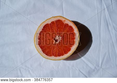Cut Half Bright Red Orange Half Grapefruit On White Drapery With Folds In Sunlight, Sheet