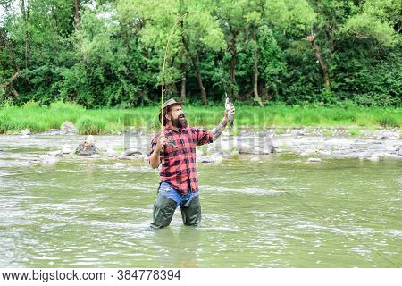 Good Things For Good Moments. Hobby And Sport Activity. Bearded Fisher In Water. Fisherman Show Fish