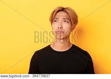 Close-up Of Sad And Disappointed Handsome Asian Guy Sulking Upset, Looking Upper Left Corner With Re