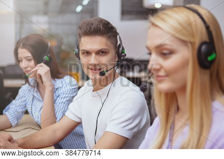 Young People Working At Call Center, Wearing Headsets With Microphones, Answering Calls. Handsome Ch