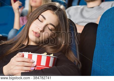 Taking A Nap. Closeup Shot Of A Gorgeous Young Woman Sleeping Holding Her Popcorn Bucket At The Movi