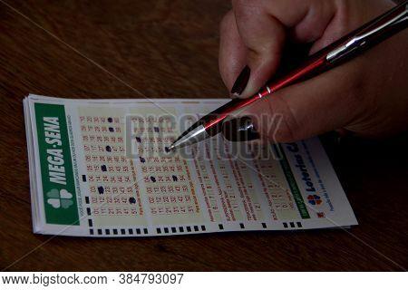 Salvador, Bahia / Brazil - December 10, 2013: Bookmaker Marking Ticket Of The Game Mega Sena, Lotter