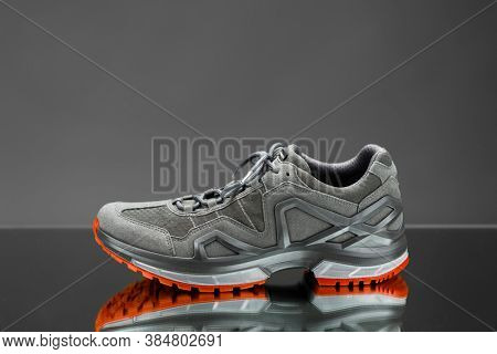 trekking sneaker with red sole, gray background