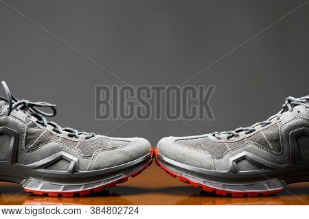 trekking sneakers with red sole, gray background with copy-space