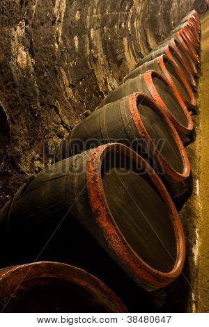 Row Of Wine Barrels In Winery Cellar Recedes Into The Distance