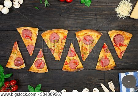 Tasty Hot Pizza With Ingredients And Pizza Cutting Knife On A Black Texture Background. Top View