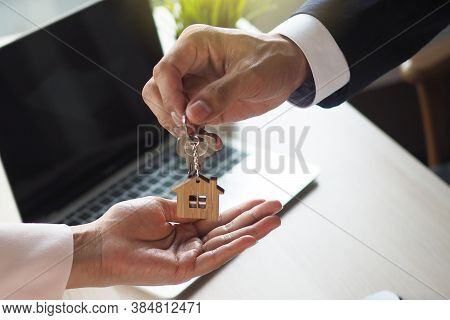 Tenant With The Landlord. Home Salesmen Are Looking At Home Keys To Buyers According To A Rental Agr