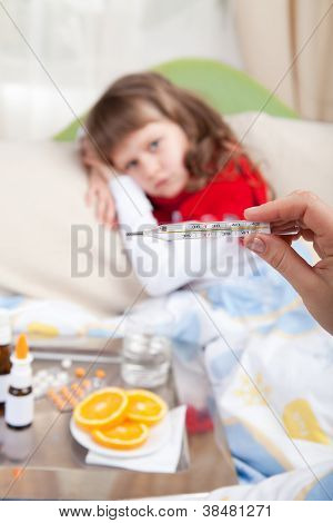 Clinical Thermometer In Hand Showing Fever And Little Sick Girl