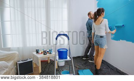 Young Family Painting Apartment Wall While Redecorating With Roller Brush. Apartment Redecoration An