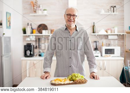 Smiling Senior Man In Home Kitchen Looking At Camera With Variety Of Tasty Cheese And Grapes On Tabl