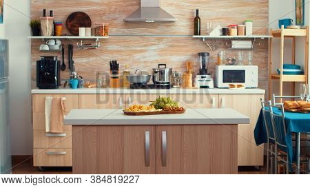 Classic Modern Kitchen With Table In The Middle Of It, Nice Wooden Details And Parquet Floor. Dinner