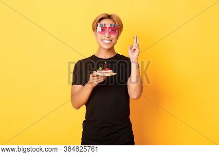 Portrait Of Hopeful Attractive Asian Birthday Guy, Celebrating In Funny Party Glasses, Holding Cake