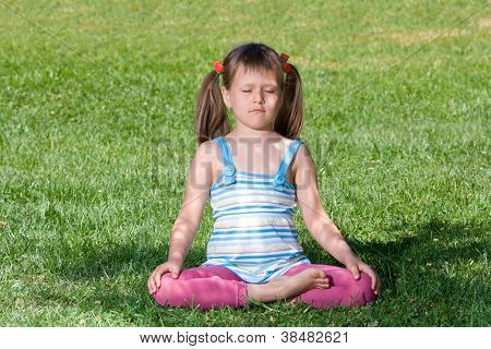Little Child Sit And Meditate In Asana On Green Grass