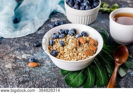 Granola With Blueberries In White Plate And Cup Of Tea For Breakfast, Homemade Baked Muesli With Nut