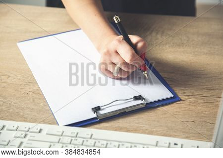 Business Woman Writes On Blank Paper On Wooden Table Background.
