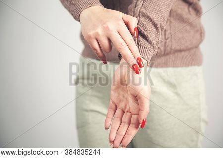 Woman Hand In Ache Wrist On Gray Background.