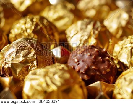 Chocolate Balls In Gold Foil View From The Top, One Praline In Open Wrapper Foil