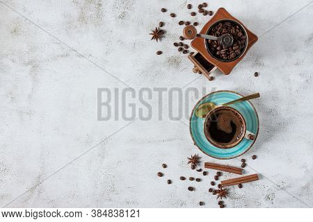 A Cup Of Coffee With Cinnamon, Anise Spices And Vintage Coffee Grinder Top View. Coffee Cup And Bean