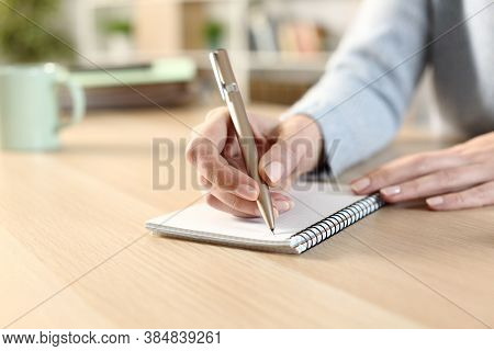 Close Up Of A Woman Hand Witing On A Notepad Sitting On A Desk At Home