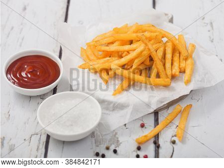 French Fries Chips On White Paper With Salt And Tomato Ketchup On Light Wooden Table Background.