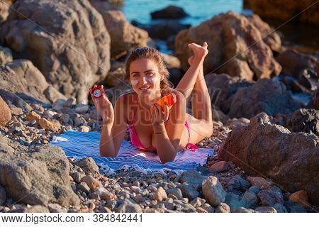 Sunbathing And Beach Day. Sun Protection. Female Relaxing On Cloth Holding Sunblock And Red Clock. R