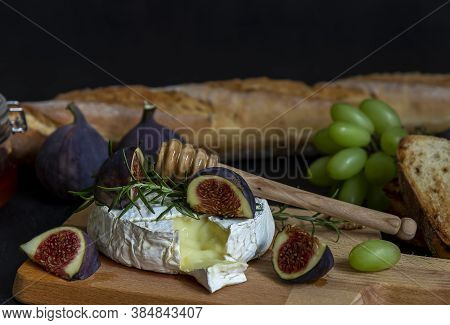 Selective Focus Of Mouthwatering Oven Baked Camembert With Walnuts, Honey, And Figs. Branch Of Green