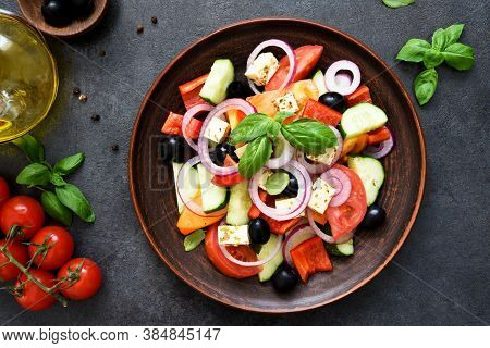 Greek Salad With Feta And Olives On A Black Concrete Background. View From Above.