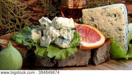 Slices Of Blue Cheese On A Green Lettuce Leaf With Figs, Grapefruit And A Stack Of Brandy On A Woode