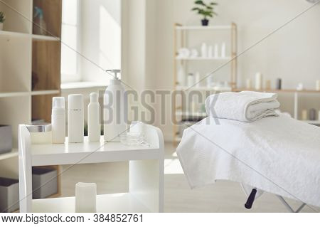 Spa Room Or Beauty Salon With Set Of Organic Skincare Products And Empty Bed With Fresh Towels