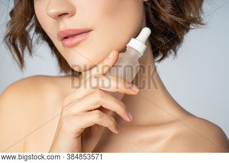 Cheerful Young Woman With Cosmetic Serum For Face