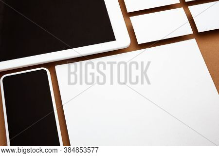 Device With Blank Screen Floating Above Brown Background. Phone, Tablet And Cards. Office Styled, Mo