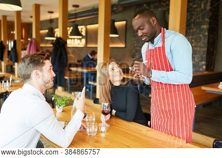 African waiter records order of guests couple on a notepad