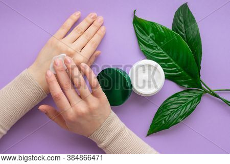 Girls Hand Is Nearby Jar With White Soft Hand And Body Cream On Purple Background With Large Green L