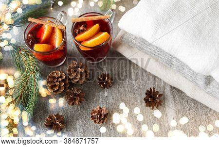 christmas and seasonal drinks concept - hot mulled wine with orange slices and aromatic spices, pine cones, fir branches and pile of knitted clothes on grey background