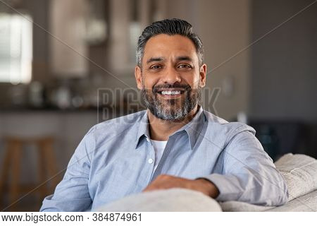 Portrait of happy mid adult man sitting on sofa at home. Handsome latin man in casual relaxing on couch and smiling. Cheerful indian guy looking at camera.