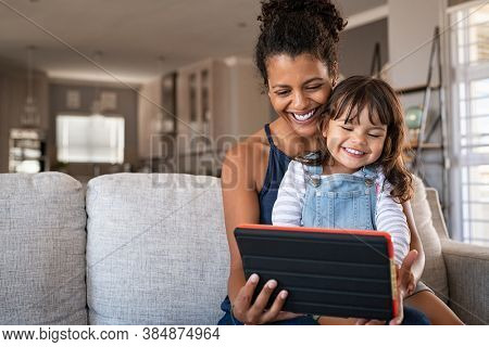 Black young mother and little daughter using digital tablet on couch. Portrait of happy african woman and her cute little girl sitting on sofa together and doing video call on digital tablet.