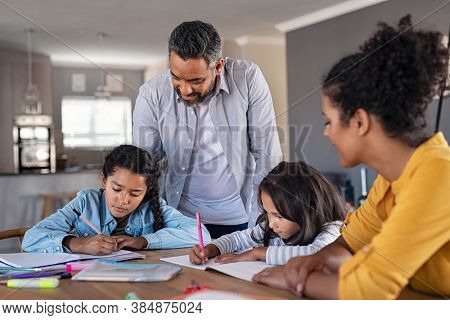 Indian parents helping children with their homework at home. Middle eastern father and african mother helping daughters studying at home. Little girls completing their exercises with the help of dad.