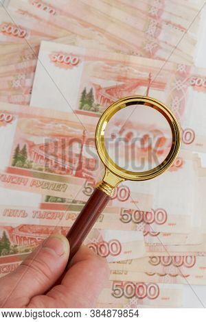 A Man's Hand Holds A Magnifying Glass With A Gold Handle Over A Large Number Of Russian Banknotes Wo