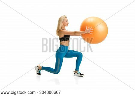 Fit Ball. Beautiful Female Fitness Coach Practicing Isolated On White Studio Background, Showing Exe