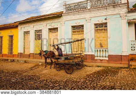 Trinidad, Cuba - December 18, 2016: Horse Carriage On The Cobblestone Streets With The Colorful Hous