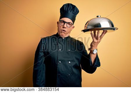 Middle age handsome grey-haired waiter man wearing cooker uniform and hat holding tray In shock face, looking skeptical and sarcastic, surprised with open mouth