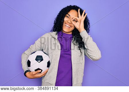 African american curly player woman playing soccer holding football bal over purple background with happy face smiling doing ok sign with hand on eye looking through fingers