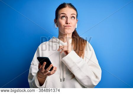 Young redhead sportswoman doing sport listening to music using earphones and smartphone Thinking concentrated about doubt with finger on chin and looking up wondering