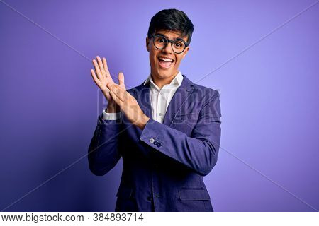 Young handsome business man wearing jacket and glasses over isolated purple background clapping and applauding happy and joyful, smiling proud hands together