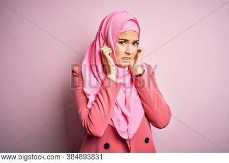 Young beautiful girl wearing muslim hijab standing over isolated pink background covering ears with fingers with annoyed expression for the noise of loud music. Deaf concept.